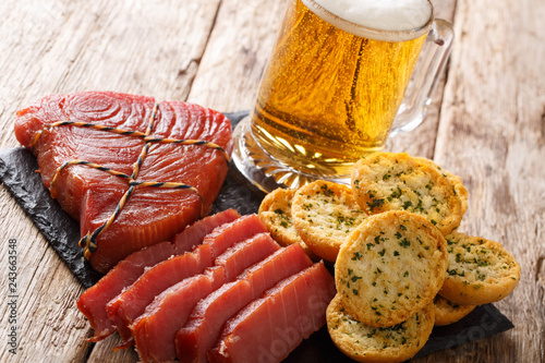 Snack to beer smoked tuna and croutons with garlic and greens closeup. horizontal
