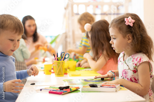 Kindergarten kids three years old on developing class play with plasticine