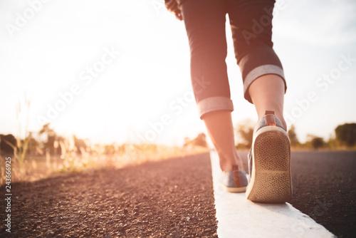 Obraz Closeup woman walking towards on the road side. Step concept. - fototapety do salonu