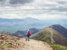 A Hiker And Their Dog Walking Down From The Summit Of Sail With Scar Crags And Causey Pike In The Distance. English Lake District, UK.