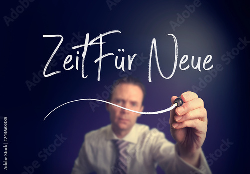 """Photo  A businessman writing a Time For New """"Zeit für neue"""" concept in German with a white pen on a clear screen"""
