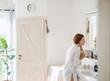 canvas print picture - A young woman putting on a make-up in the morning in a bathroom.