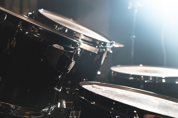 Closeup view of a drum set in a dark studio. Black drum barrels with chrome trim. The concept of live performances