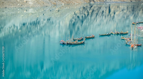 Valokuva  Docked boats in the turquoise Attabad lake with reflection of mountain