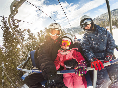 Fotografía happy smiling family skiers on ski lift making selfie
