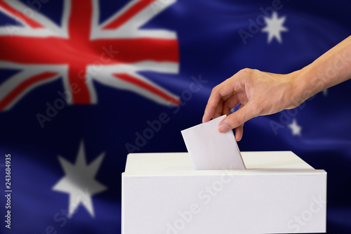 Fotografia, Obraz  Close-up of human hand casting and inserting a vote and choosing and making a decision what he wants in polling box with Australia flag blended in background