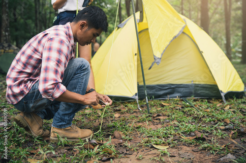 Tuinposter Zwavel geel Camp in the tent - Man setting a tent on the camping. Man setting a camping tent.Man on camping trip in countryside.