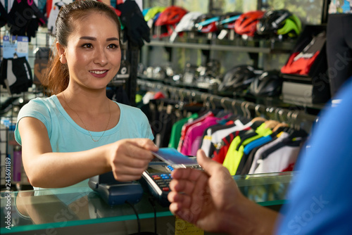 Smiling sports shop customer paying for purchase with credit card
