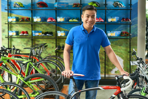 Portrait of smiling Vietnamese handsome bicycle store manager
