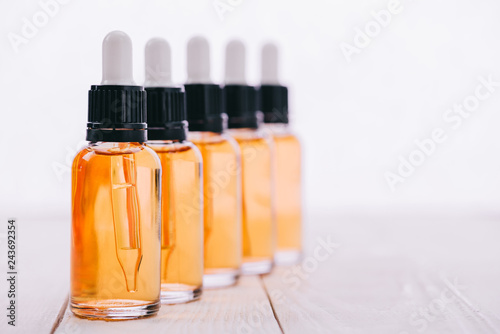 Fototapeta selective focus of cbd oil in bottles with droppers on wooden surface isolated on white obraz