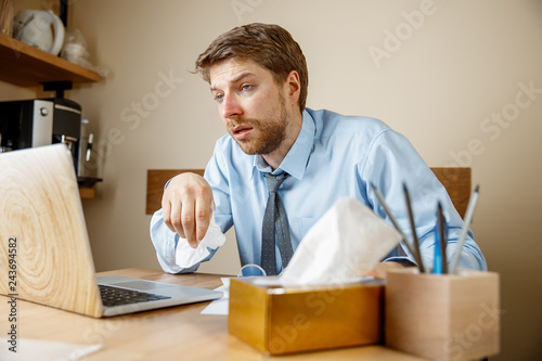 Photo  Sick man with handkerchief sneezing blowing nose while working in office, businessman caught cold, seasonal flu