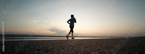 Foto auf Leinwand Jogging Woman running with sunset or sunrise background