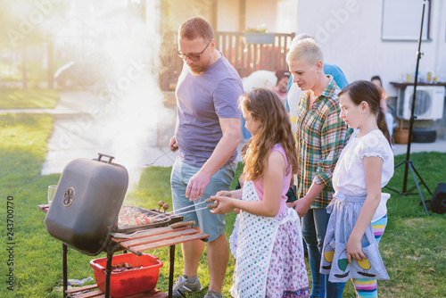 Proud happy father learning his daughter how to make a barbeque. Big happy family in their backyard.