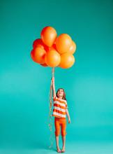 Cute Girl Holding Orange Ballo...