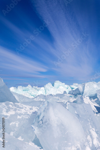 Blue ice blocks and hummocks under a blue sky with stratus clouds. Natural winter ice cold background. Lake Baikal in February