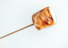 Roasted Marshmallows On A Skewer In Female Hand On White Background