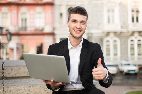 Photographie  Young smiling businessman in classic black suit and white shirt with wireless ea