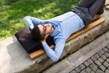 Young Handsome Man In Blue Shirt And Sunglasses With Wireless Earphones Dreamily Lying On Bench While Spending Time In City Park