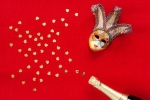 Venetian Mask And Champagne Bottle With Heart Shape Gold Glitter Confetti. Top View, Close Up On Red Background