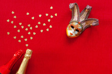 Venetian Mask And Two Champagne Bottles With Heart Shape Gold Glitter Confetti. Top View, Close Up On Red Background