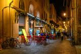 Fototapeta Uliczki - Old narrow street in Bologna, Emilia Romagna, Italy. Night cityscape of Bologna.