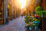 Fototapeta Uliczki - Old narrow street with flower shop in Bologna, Emilia Romagna, Italy