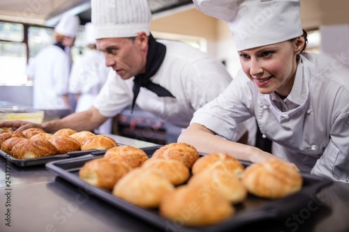 Fotografía  Male and female chefs preparing kaiser rolls in kitchen