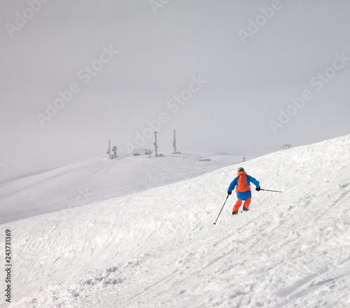 Skier descent on snowy freeride slope and overcast misty sky