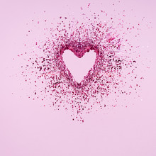 Glitter Heart Dissolving Into Pieces On Pink Background.  Valentines Day, Broken Heart And Love Emergence Concept