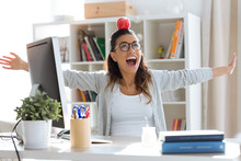 Happy Young Business Woman Having Fun And Holding Red Apple Over Her Head In The Office.