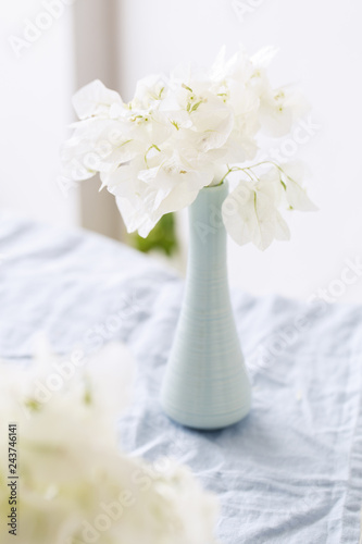 Vase with bougainvillaea flowers on the table Fotobehang