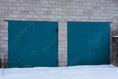 Obraz na płótnie blue metal gates on a gray brick wall of a garage outside in white snow