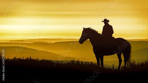 A cowboy on horseback observes the golden mountains Wallpaper Mural
