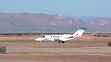 Generic Unmarked Private Jet On A Desert Runway With Mountains In The Background On A Sunny Day In The South Western United States
