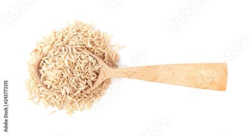 Fototapeta Spoon and uncooked brown rice on white background, top view obraz na płótnie