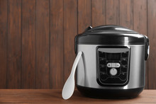 Modern Powerful Multi Cooker On Table Against Wooden Background. Space For Text