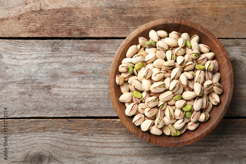 Organic pistachio nuts in bowl on wooden table, top view. Space for text