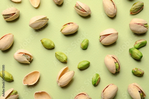 Composition with organic pistachio nuts on color background, flat lay
