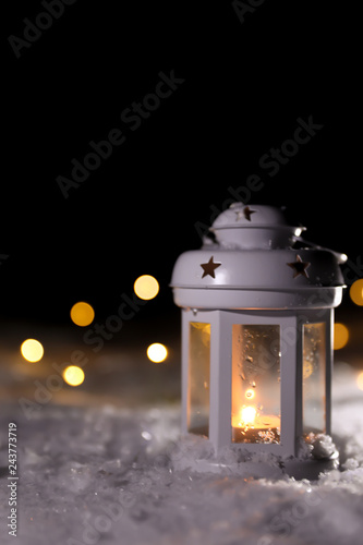Lantern with burning candle and Christmas lights on white snow outdoors
