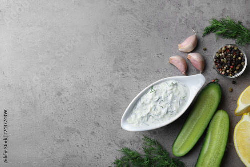 Tzatziki cucumber sauce with ingredients on grey background, top view. Space for text