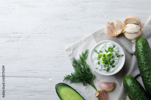 Tzatziki cucumber sauce with ingredients on wooden background, top view. Space for text