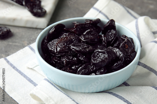 Bowl of sweet dried plums on table. Healthy fruit
