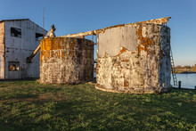 Two Large Tanks Slowly Decaying On Green Grass