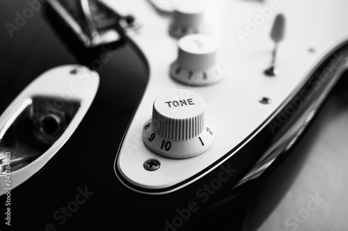 Photo  Close-up of electric guitar, in black and white.