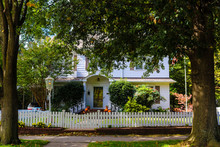 Two Story White Wood House With Picket Fence Pumpkins And An American Flag Flanked By Two Large Trees