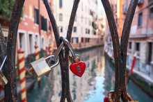 Combination Red Heart-shaped And Other Padlocks On The Bridge In Venice, Italy. Sunny Day, Historical Buildings And The Canal In The Background. Close Up. Valentine's Day Concept.