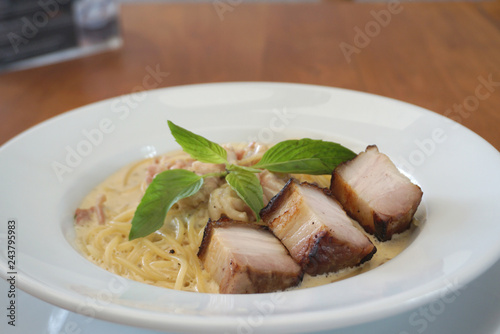 Poster Fish Spaghetti Carbonara sauce with fried chunk pork meat serving on the white plate