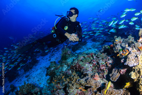 Male SCUBA diver exploring a colorful tropical coral reef in the Andaman Sea