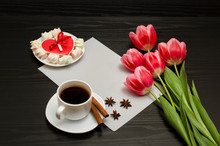 Holiday Concept. Bouquet Of Pink Tulips, A Cup Of Coffee, Red Heart-shaped Cookies With A Note, Cinnamon, Star Anise And Sheet Of Paper On A Black Wooden Background