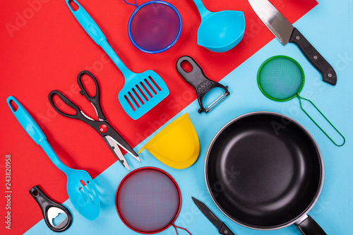Fotografía  Close up portrait of frying pan with set of kitchen utensils on red-blue backgro